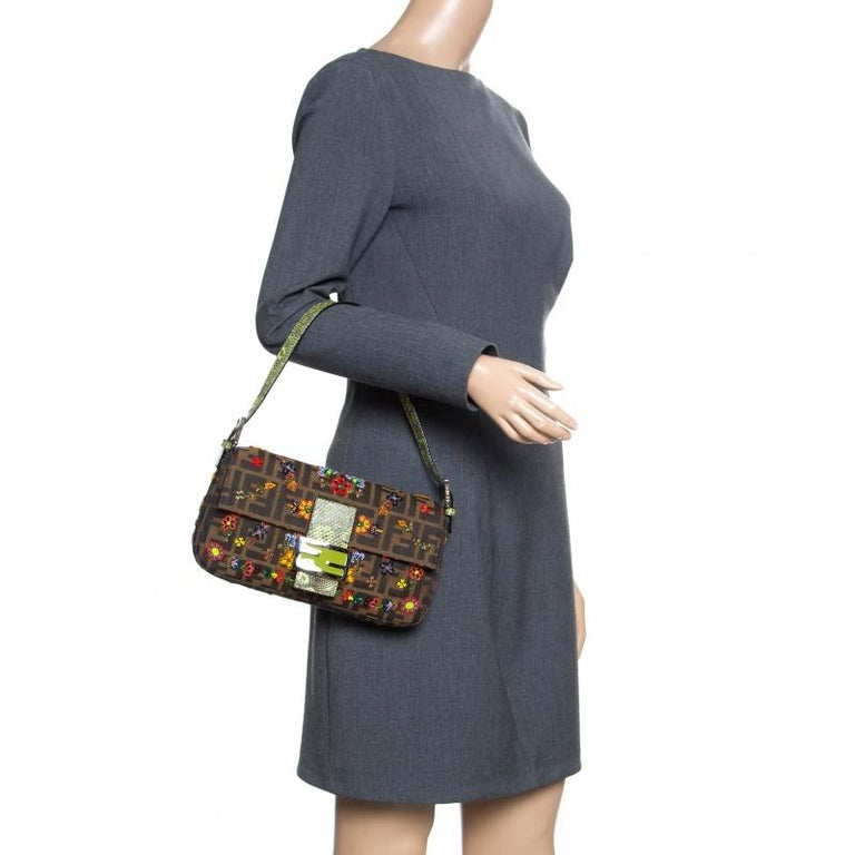 The Mama Baguette bag from Fendi is an all time classic. Accented with the striking Forever lock with Lizard trim on the front flap, the piece carries a Zucca canvas exterior that is decorated with beautiful floral bead detailing. It has a spacious