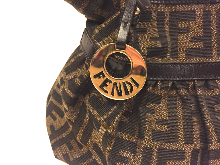 - Fendi zucca monogram small handbag. It is like a bucket shape bag.   - A silver toned round