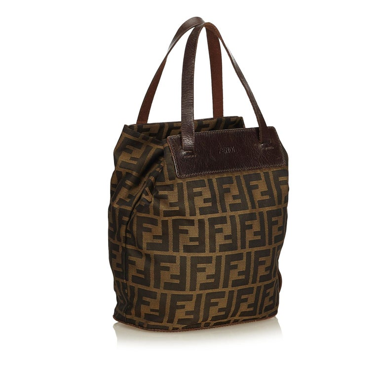 95502c06bf4c This Fendi tote bag features a Fendi logo print Zucca nylon body with  chocolate brown leather