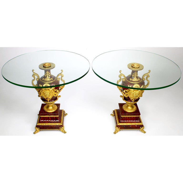A fine pair of French Louis XV style Ormolu Mounted Rouge Griotte marble urns by Ferdinand Barbedienne (French, 1810-1892), now converted to low side tables with glass tops. The ovoid shaped urns surmounted with finely chased allegorical ormolu male