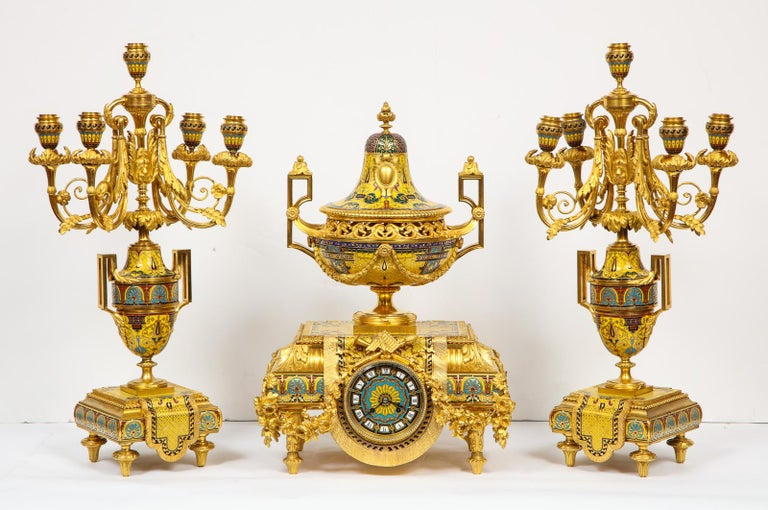 Ferdinand Barbedienne, A Museum Quality French Ormolu Champleve Enamel three-piece Clock Set Garniture.  Comprising of a clock and a pair of Candelabra, with the highest quality French ormolu or bronze and champleve cloisonne enamel.  The clock in