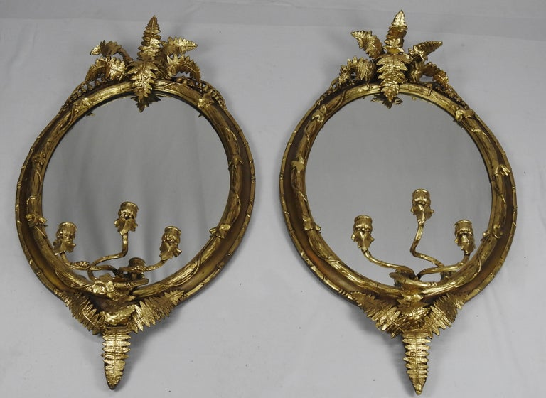 Offering this stunning pair of French fern leaf mirrors. Water gilt highlighting the fern leaf and candleholders.