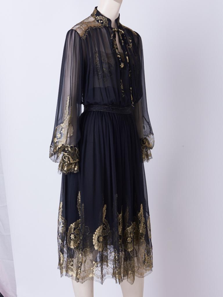 Ferragamo black silk, georgette peasant style dress with a chiffon under pinning. Dress has gossamer gold  lace detail at cuffs, sleeves, shoulders, and hem. Mandarin style collar, with tie.
