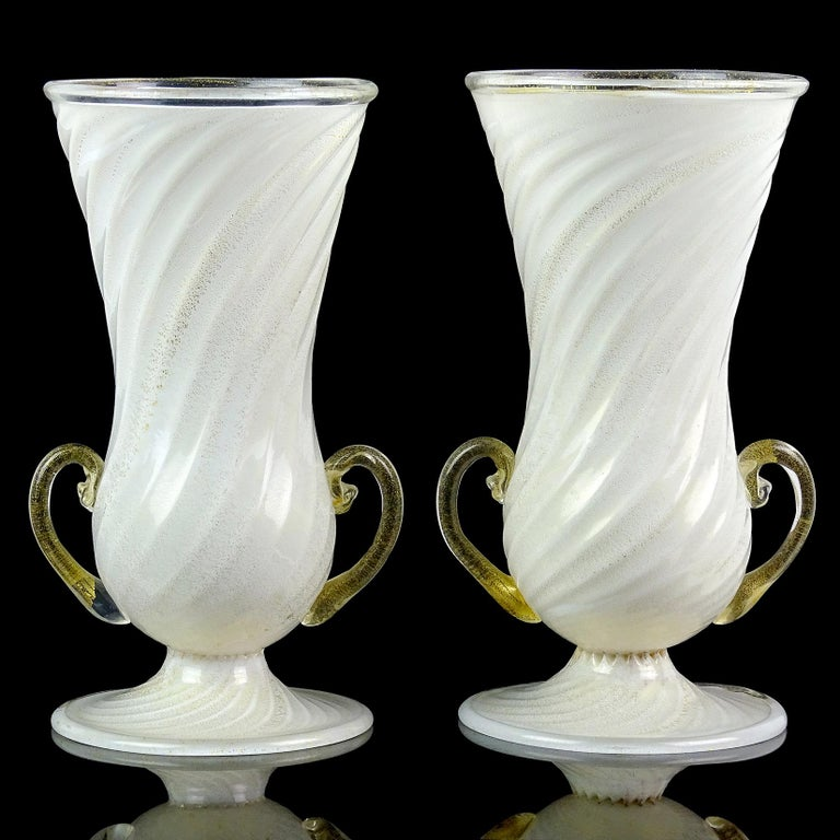 Beautiful and rare, matching antique Murano hand blown white and gold flecks Italian art glass double handles flower vases. Documented to the Ferro Toso Barovier Vetreria Artistiche Riunite S. A. company, circa 1939-1942. One of the vases still