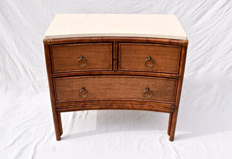 Ficks Reed caned bamboo chest of three dovetailed drawers with attractive inverted curved front design, leather accents and heavy brass hardware. Thick attached marble top adds versatility for a variety of practical and aesthetically pleasing