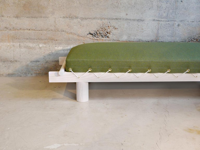 The Field bed by Hinterland Design is a modern take on the army cot. Made of solid Canadian white ash, the frame is then whitewashed and topped with an overstuffed wool upholstered cushion. This day bed's cushion is then lashed to the frame with
