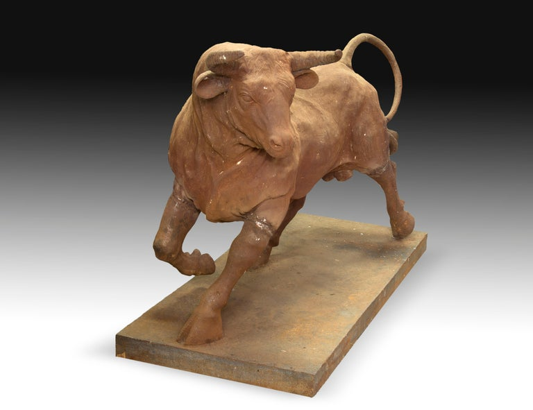 Iron sculpture located on a rectangular base that shows a fighting bull walking. They emphasize the naturalness in the posture, anatomy and details of the animal. Size: 60 x 130 x 90 cms.