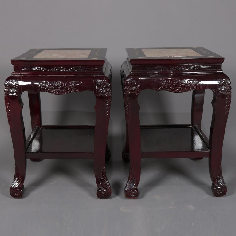 A pair of figural Chinese end table feature inset marble top with mother-of-pearl inlay featuring doves (birds) and foliate elements surmounting hardwood base having carved foliate skirts and raised on legs with figural bird head masks and acanthus