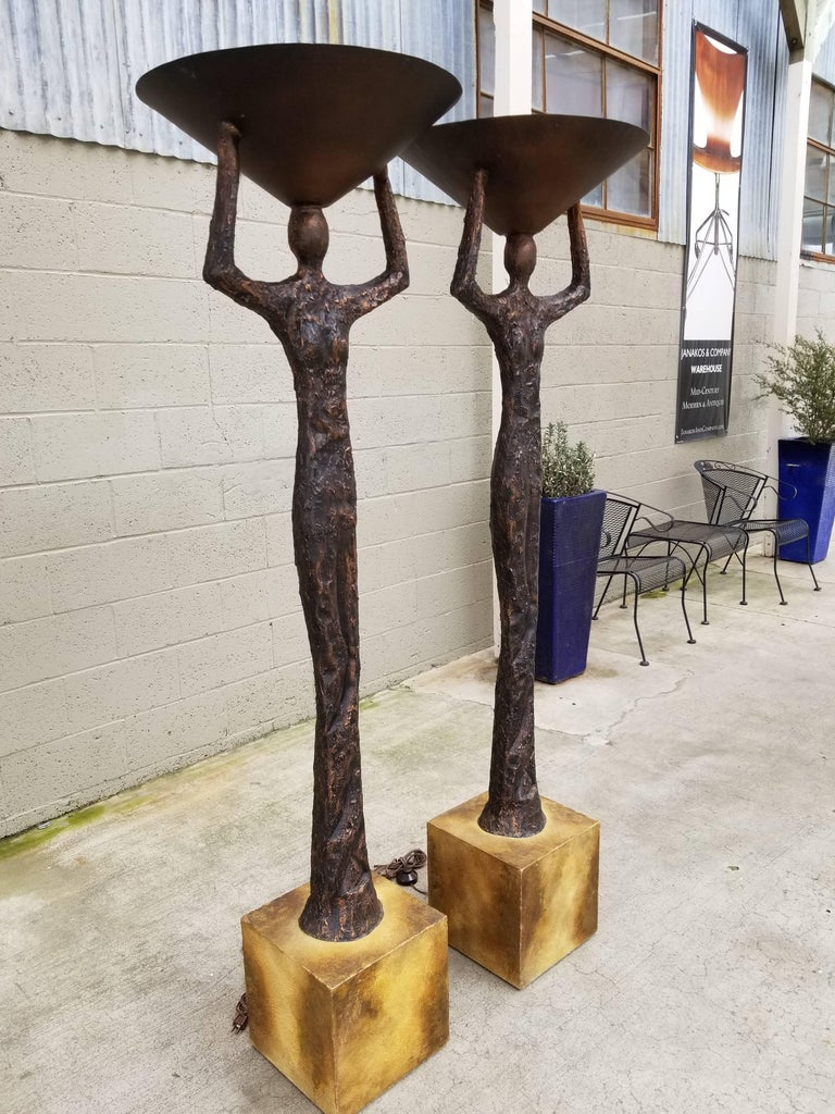 A pair of torchiere floor lamps in the manner of Alberto Giacometti. Heavily textured finish resembling patinated bronze. Wood bases with steel weights. Steel cone shades. Figures are a hallow fiberglass with applied resin for texture. Impressive
