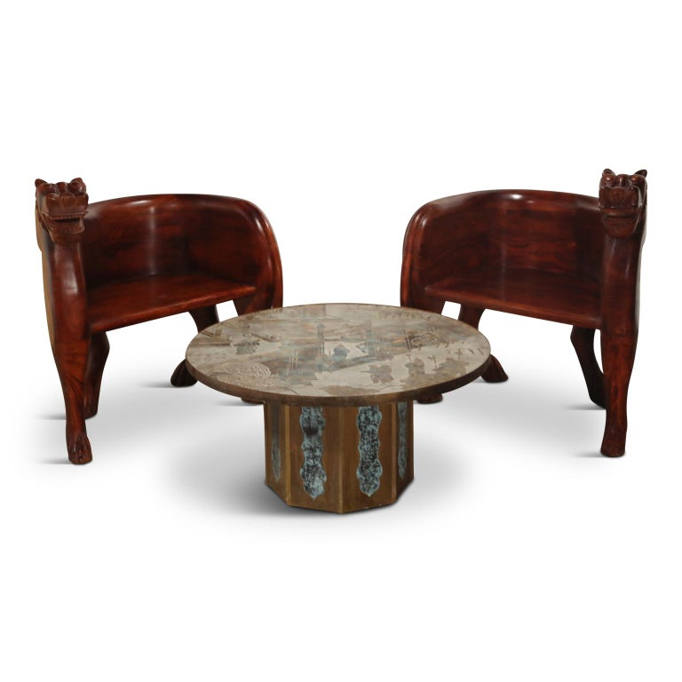 This spectacular pair of hand carved teak lioness club chairs are front-cover-magazine-worthy and can add a bit of the unexpected to any style of room. The color is a deep reddish brown that more closely resembles rosewood or Brazilian Jacaranda