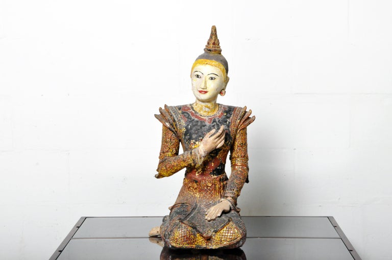 A finely carved wooden sculpture of a Buddhist angel in the Northern Thai style. It is covered in natural lacquer, gold leaf, polychrome, and glass mirror