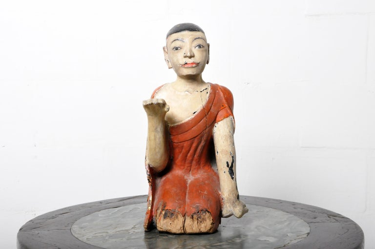 A teak wood figure of a young monk in a posture of devotion and with a facial expression is one of piety and innocence. The piece is covered in natural red cinnabar lacquer and polychrome. There is some damage to the wood from moisture; this is