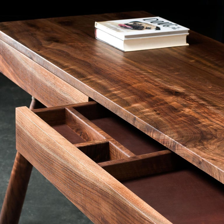 Our FIJN desk is handcrafted in solid wood. Both desks pictured were built in figured Oregon black walnut. Solid wood drawers are lined in leather and inserts can be customized to suit.  Hand-turned legs attach to the desk top in steel cuffs.