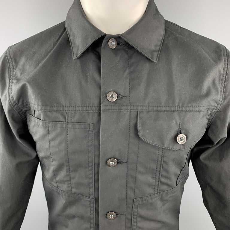 FILSON Trucker Jacket comes in a black tone in a solid coated cotton material, with patch pockets, buttoned cuffs, lined, button up. Made in USA.   Excellent Pre-Owned Condition. Marked: XS  Measurements:  Shoulder: 16.5 in.  Chest: 38 in.  Sleeve: