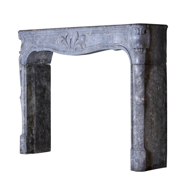 This vintage fireplace surround is made of grey-blue bicolor Burgundy hard stone. It bears a flower motif on the fronton. A great mantel (fireplace), one in his kind. Measures: 157 cm EW 61.81