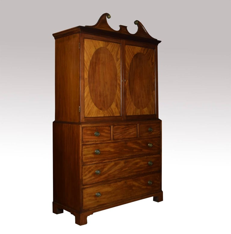 Fine 18th century George III period mahogany gentleman's cabinet on chest with inlaid swan neck pediment above two oval panelled doors opening to reveal five graduated draws. The base section fitted with three short and three long graduated draws