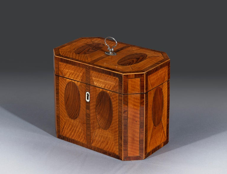 The West Indian satinwood caddy is fitted with the original silver handle and is inlaid with padouk and crossbanded and inset with oval panels throughout. The hinged top opens to reveal two glass tea canisters fitted with the original side caps. The