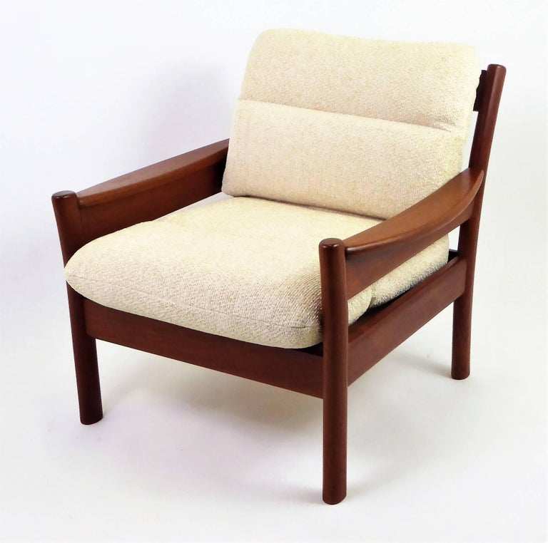 Fine 1960s Dyrlund of Denmark solid teak armchair with fitted cushions in new woven Chenille in a neutral cream color. Warm, rich, solid Teak all around with unique carved legs and wide shaped armrests. Slatted back. Dyrlund label. New Pirelli