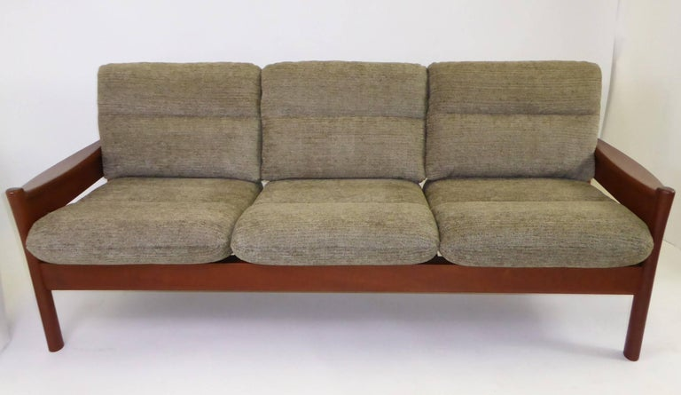 Fine 1960s Dyrlund of Denmark solid teak sofa with fitted cushions in new woven Chenille fabric in a olive green color. Warm, rich, solid Teak all around with unique carved legs and wide shaped armrests. Slatted back. Stylistically, very much like