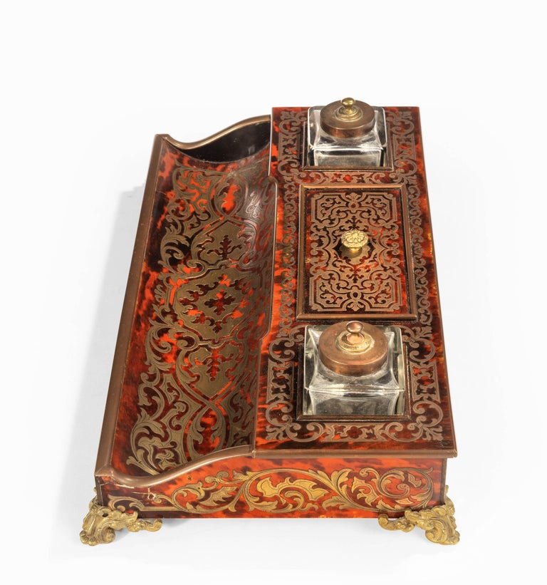 A fine Boulle 19th century desk set in excellent overall condition. The particularly right coloured tortoiseshell surfaces profusely made with cut brass and retaining the original square section inkwells.