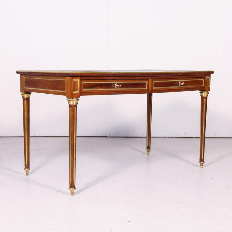 A fine 19th century French Louis XVI style bureau plat or desk handcrafted of mahogany by talented artisans near Lyon, circa 1880s. Having the original black tooled leather top above two drawers, this handsome desk features gilt brass trim and