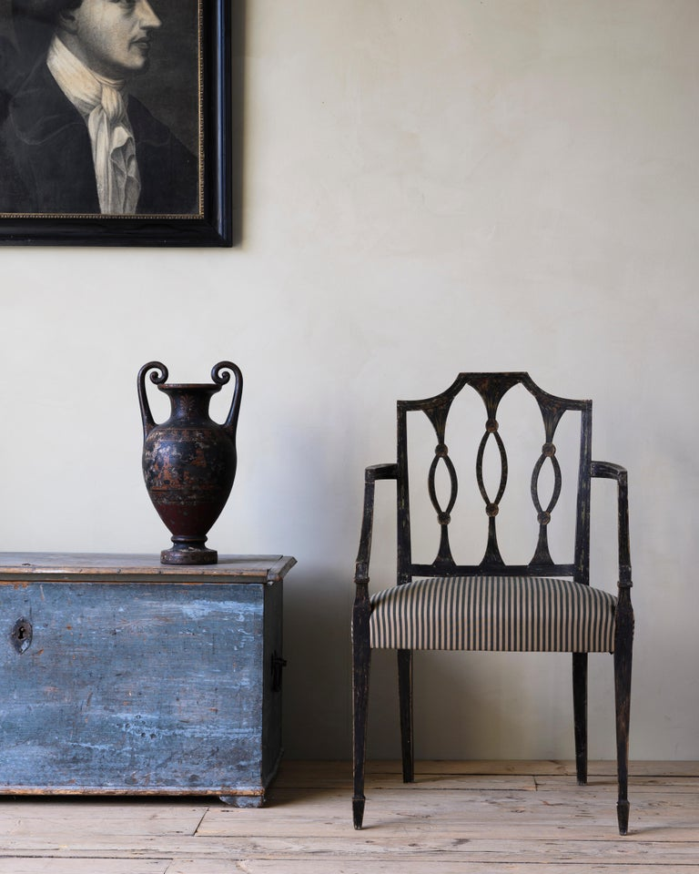 Fine and unusual early 19th century late Gustavian / early Empire armchair in neoclassic style. Original condition with delicate flower painting on the backrest, circa 1815, Sweden.