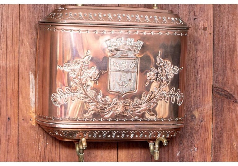 French repoussé copper lavabo has an elaborate coat of arms on the front of the upper storage tank where the water is held. A bronze spigot allowed the water to empty into the bottom basin by turning it to the right or left. The lower basin has