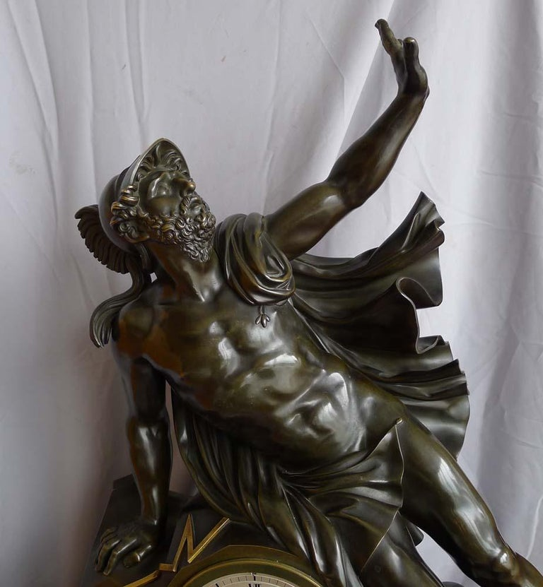 Fine and large antique Charles X mantel clock of Ajax. The clock features the magnificent figure of the Trojan warrior Ajax leaning upon the clock case. He is wearing a cloak and his war helmet. The clock has been made of well patinated bronze and