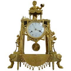 Fine and Rare French Empire Clock of Cupid as Magician Uncovering Flaming Hearts