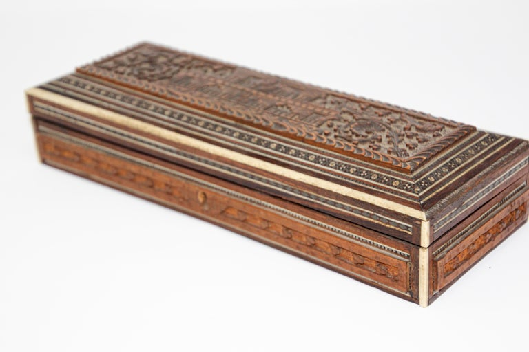 Fine antique Anglo-Indian hand carved wooden jewelry box inlaid with mother of pearl, bone and precious wood. Box with a palace architectural motif design intricately carved. Mother of pearl, satinwood adorn this exquisite 19th century inlay