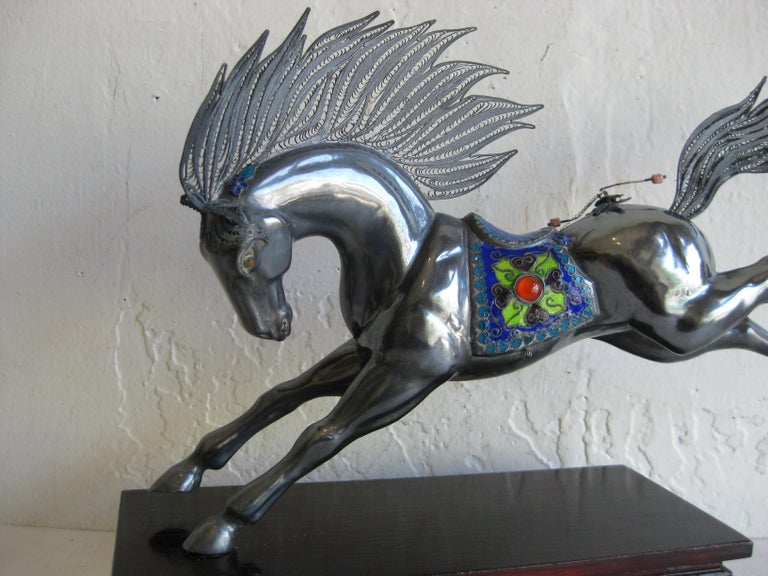 Fine antique Chinese sterling silver and enamel horse sculpture mounted on a lacquered wood stand. The horse is made of sterling silver and is made well. Has enamel decorations as seen in the photos. Also coral beads as decorations. Missing one
