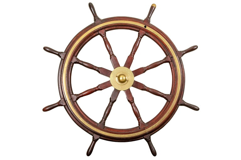 Antique ships wheel. Constructed of Mahogany and brass, with one grip having a brass cap.  Condition: Some slight pitting and tarnish to the brass, wear to the wood on the grips and some on the frame, as expected with use and age.