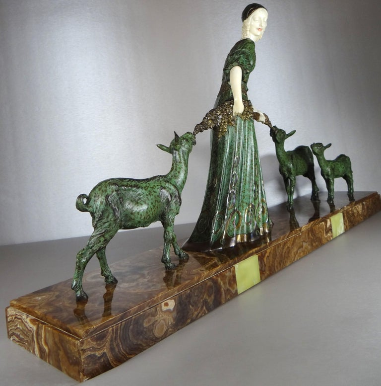 A fine cold painted spelter and ivoreen Art Deco figural group by Demetre Chiparus (1886-1947), a woman in a flowing green dress and a modish cloche, with ivoreen arms and painted face, accompanied by three goats nibbling at flowers, raised on a