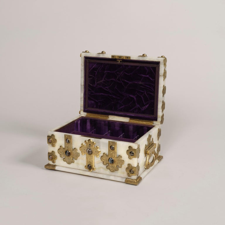 An fine onyx toilet box by George Betjemann & Sons  The case constructed in a fine solid onyx having a continuous grain on all its facets, of rectangular form raised on a stepped base. The brass guard strapping, filigree corner brackets and side
