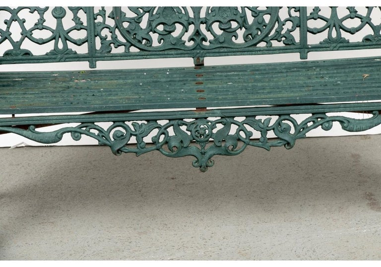 A very fine iron bench in Belle Époque style. The iron bench in old green paint, worn in places to reveal older white and red paint. With an elaborate openwork arched back with center fan and trefoil motifs, flanked by leafy motifs. The sides, skirt