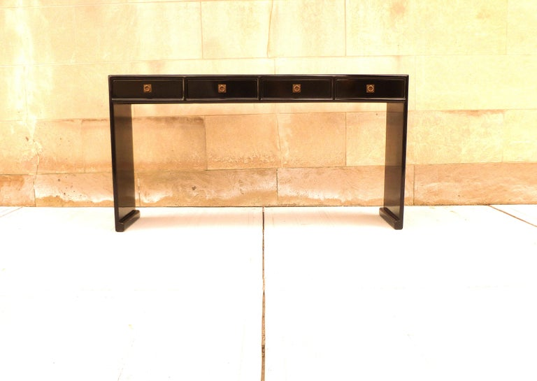 Fine black lacquer console table with four drawers, waterfall legs, brass fitting, elegant and simple form, beautiful lines. We carry Fine quality furniture with elegant finished and has been appeared many times in