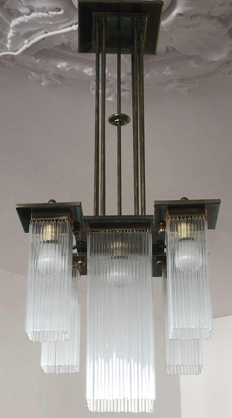 A beautiful and very elegant 5-light brass and glass chandelier in the style of Koloman Moser and Otto Wagner, circa 1990s, Austria, Vienna. The chandelier needs E27 standard screw bulbs for illuminate. Excellent condition.