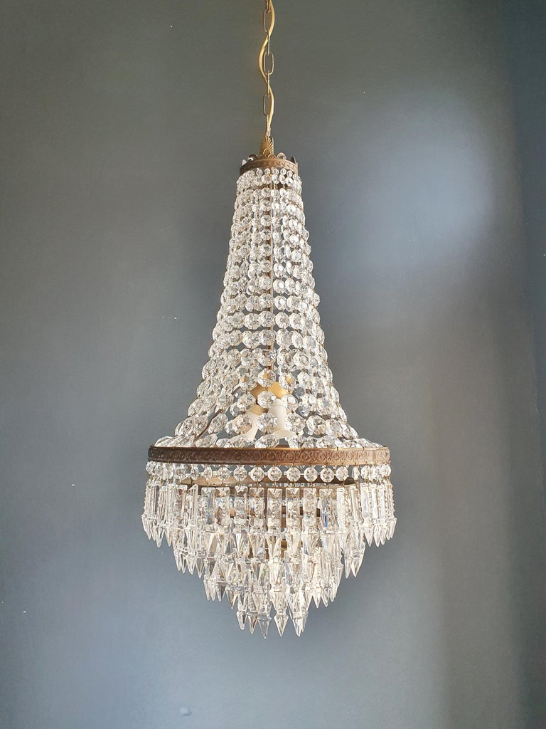Cabling and sockets completely renewed. Crystal hand knotted Measures: Total height 110 cm, height without chain 72cm, diameter 35 cm, weight (approximately) 6 kg.  Number of lights: 3-light bulb sockets: E14  Fine brass Empire Sac a pearl