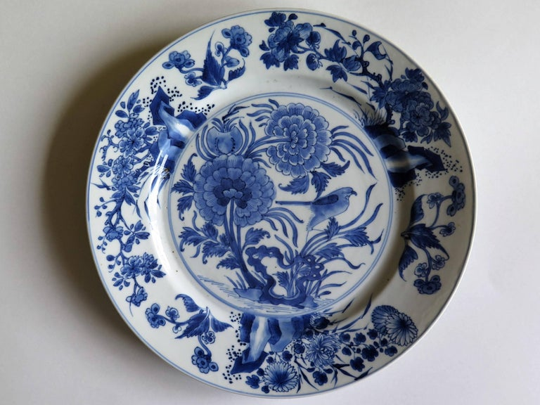 This is a beautifully hand-painted Chinese porcelain blue and white plate from the Qing, Kangxi period, 1662-1722.  The plate is finely potted with a carefully cut base rim and a lovely rich glassy, very light blue glaze.  The plate is carefully