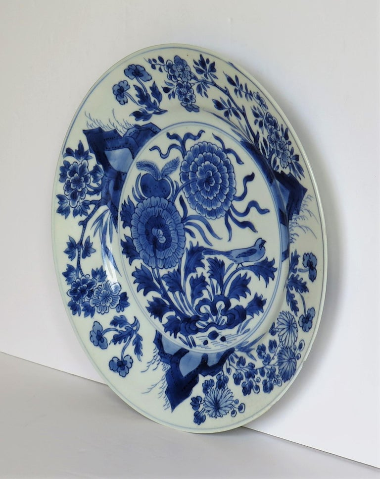 This is a beautifully hand painted Chinese porcelain blue and white plate from the Qing, Kangxi period, 1662-1722.  The plate is finely potted with a carefully cut base rim and a lovely rich glassy white glaze, with a very light blue tinge.  The