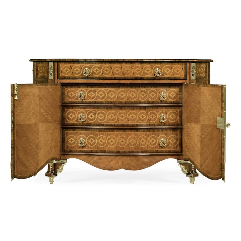 A fine Chippendale style crossbanded and marquetry inlaid chest of drawers with cast brass mounts after a Thomas Chippendale original, the detailed serpentine doors opening to reveal three further graduated drawers within. With elaborate inlays,