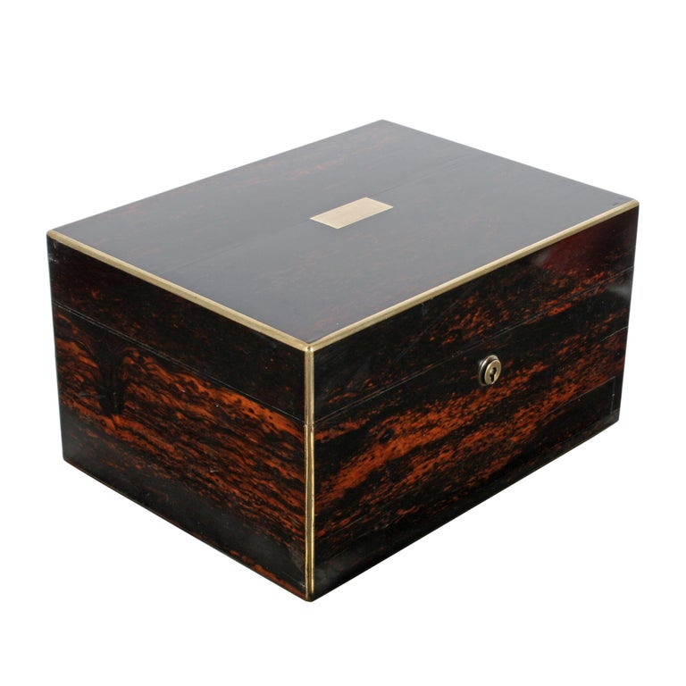 A mid-19th century Victorian coromandel wood veneered and brass edged jewellery or dressing box.  The box has a fitted interior with sterling silver topped bottles and jars.  To the front of the box is a spring drawer that is silk lined to hold