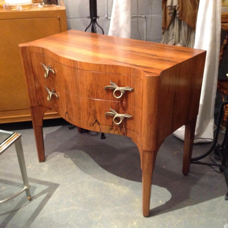 Superb quality signed by the maker. Fashioned with exquisite rosewood veneers and serpentine front. The petite commode is appointed with stunning doré hardware.