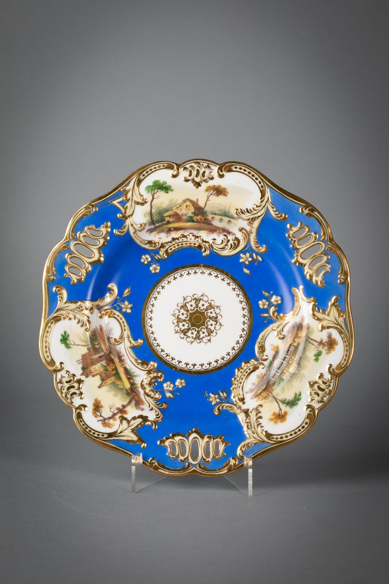 Comprising 24 plates, pair of covered sauce tureens and stands, pair of shell dishes and a pair of rectangular dishes. The bright blue ground interspersed with gilt-edged reticulation and with three rococo-formed cartouches edged in scrolls, molded