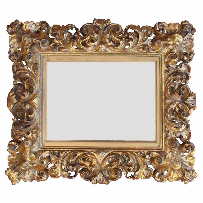 A fine Italian 19th century Baroque style Florentine giltwood carved figural mirror frame, with carvings of allegorical masks on each corner, Florence, circa 1880.
