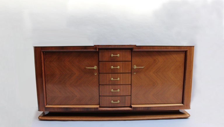 A fine French Art Deco palisander sideboard by Maxime Old, with 2 doors, 5 drawers and bronze hardware. Signed A matching dining table, 8 chairs (6 side and 2 arm), and 2 vitrines are also available, see pictures.
