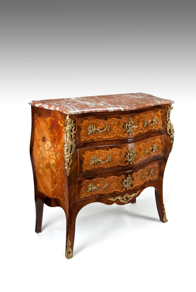 A fine quality antique French rosewood and kingwood floral marquetry inlaid pink marble topped bombe commode in the Louis XV Manner dating to circa 1910-1920.