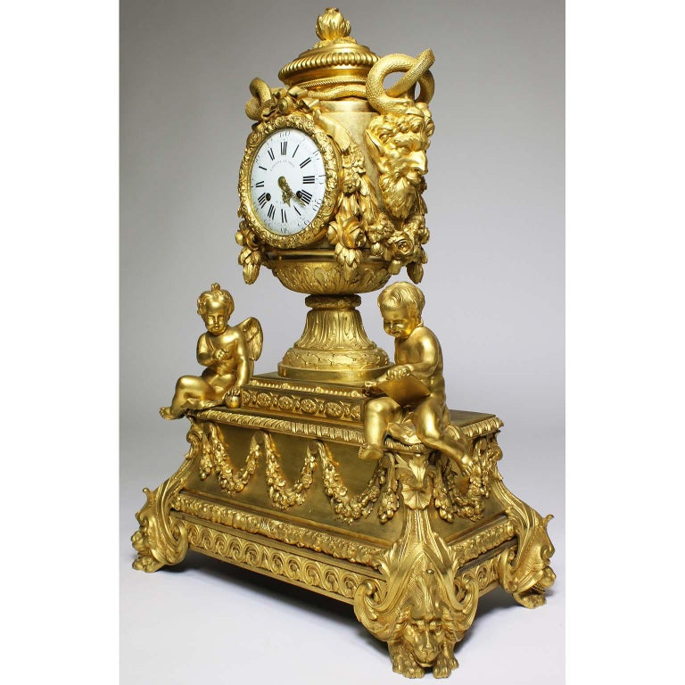 A very fine and Palatial French Louis XVI style figural gilt bronze mantel clock. The vase shaped case surmounted with a pomegranate-cast finial and flanked by large satyr mask handles fitted with intertwined gilt-bronze snakes, amongst floral