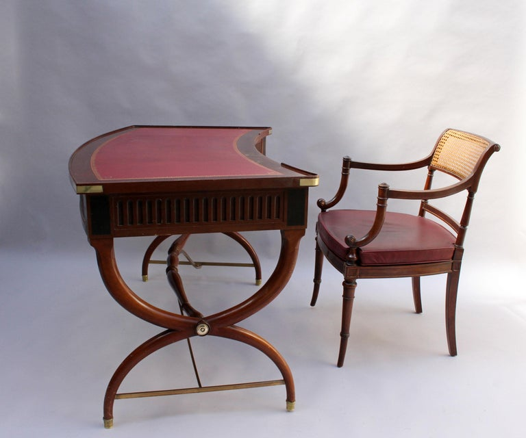 A fine French Art Deco neoclassical mahogany curved desk with 3 drawers, a red leather top, some bronze details and its original desk arm chairs.
