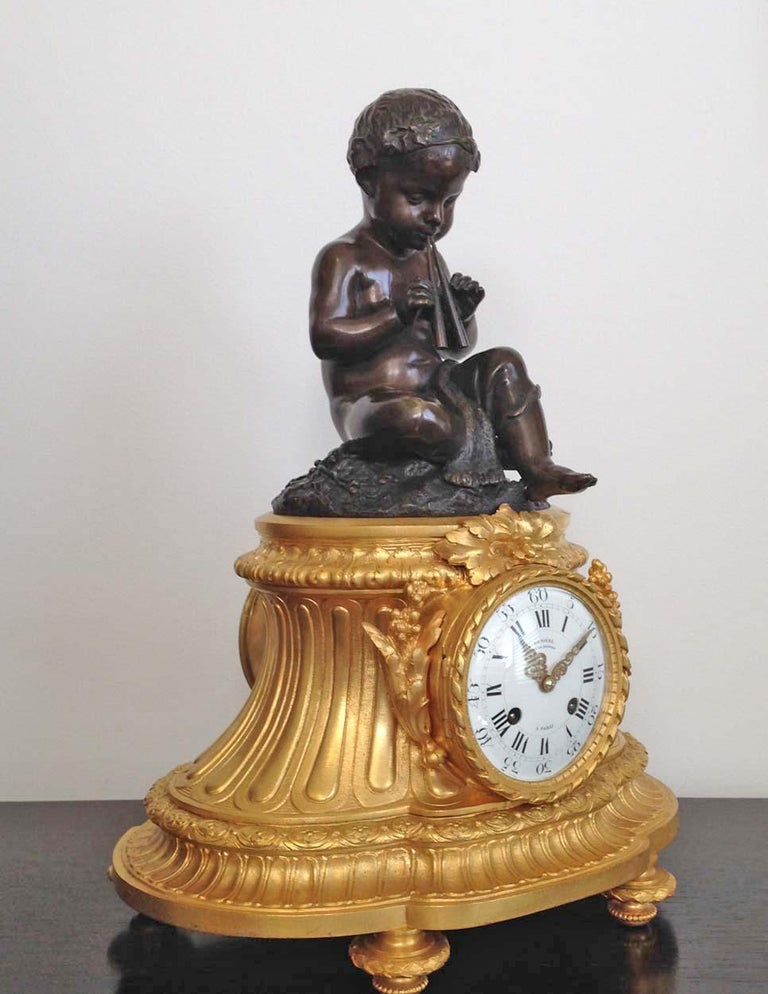 A fine French 19th Century Louis XVI style ormolu and patinated bronze clock signed by renowned Paris clock maker Denière.   Surmounted by the patinated bronze figure of a partly draped child wearing a wreath of leaves and playing an aulos (Greek
